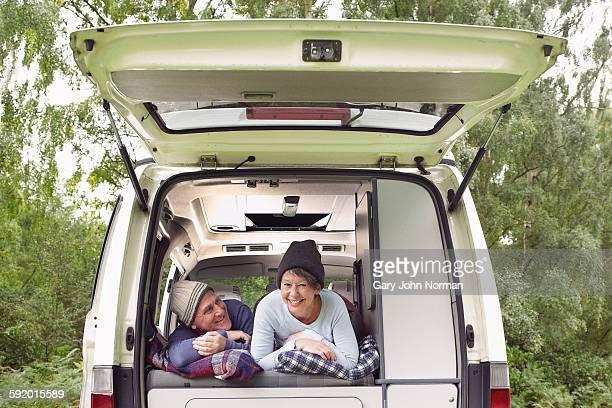 senior couple lying inside open camper van - norman elder stock photos and pictures