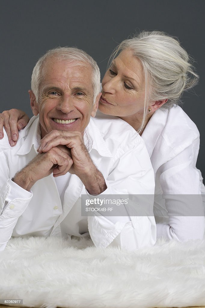 Senior couple lying on a lambskin : Stock Photo