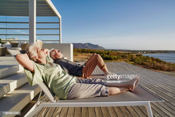 senior couple lying on deck chairs at luxury beach house - sunbathing stock pictures, royalty-free photos & images