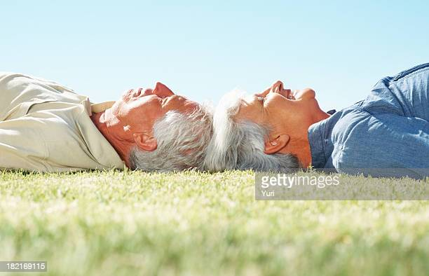 Senior couple lying on grass with heads together