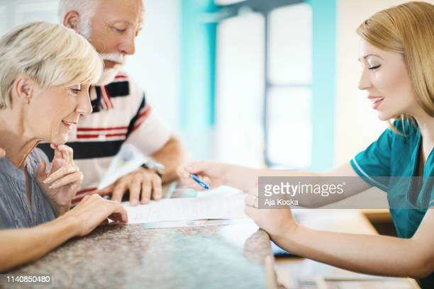 senior couple making a doctor's appointment. - medical receptionist uniforms stock photos and pictures