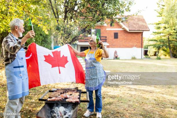 senior couple making barbecue together in their garden. - canada day stock pictures, royalty-free photos & images