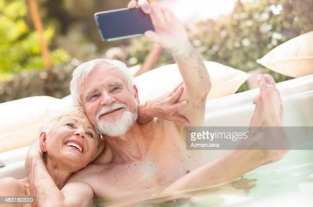 Senior couple making selfie in hot tub