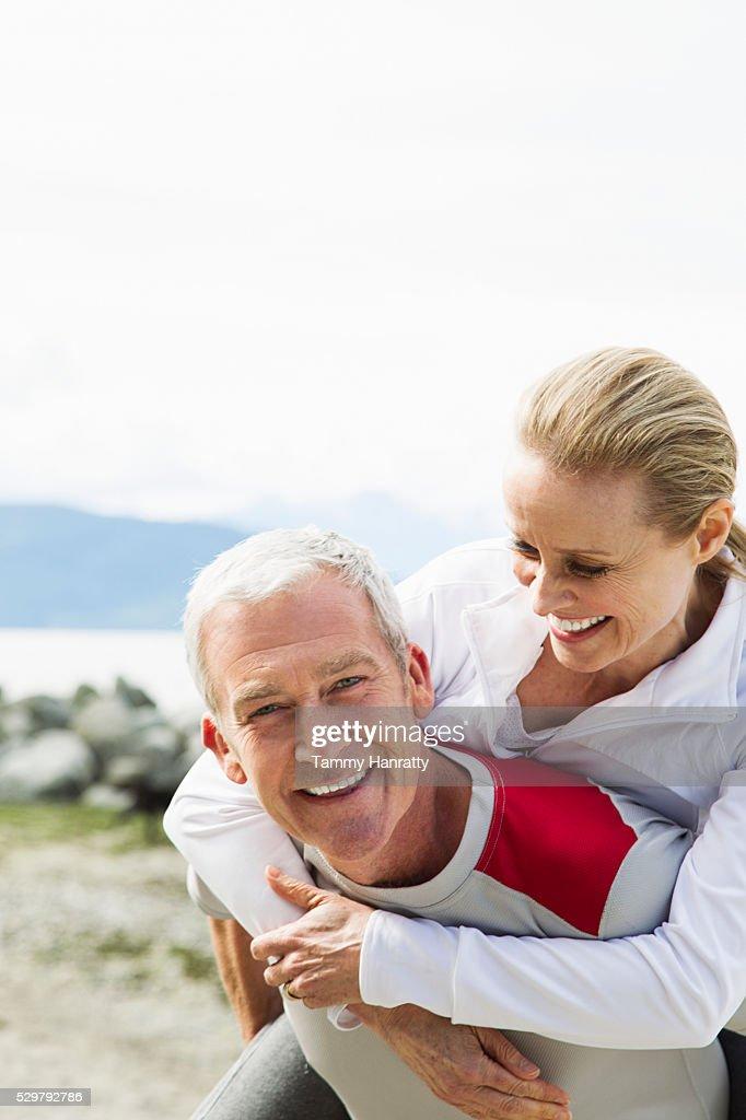 Senior couple, Man giving woman piggy back ride : Stock Photo