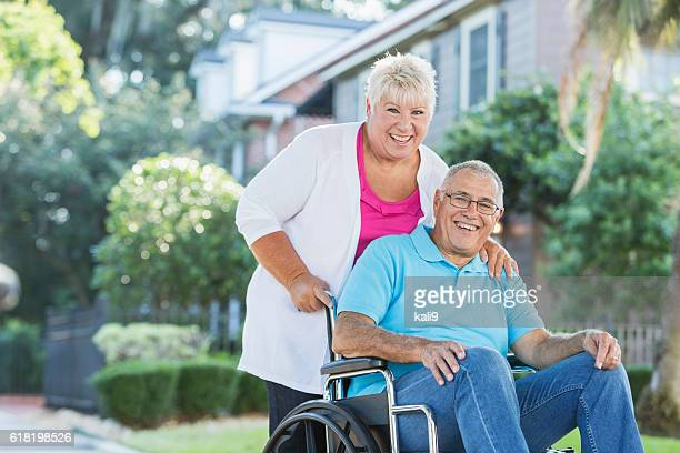 Senior couple, man in wheelchair getting fresh air