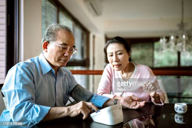 senior couple measuring blood pressure - blood pressure gauge stock pictures, royalty-free photos & images