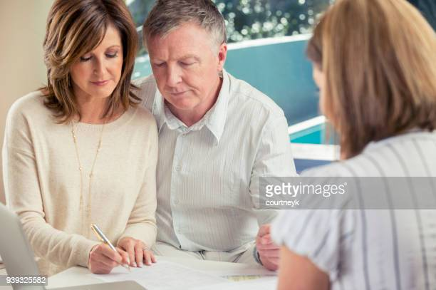 senior par de reunión con asesor financiero. - documento legal fotografías e imágenes de stock