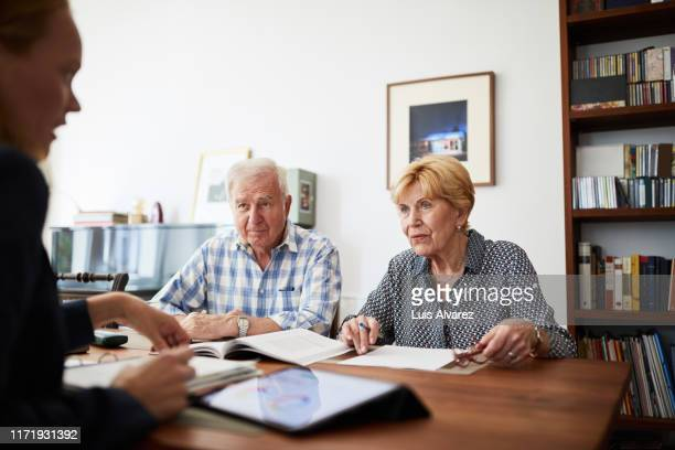 senior couple meeting with financial consultant at home - advice stock pictures, royalty-free photos & images