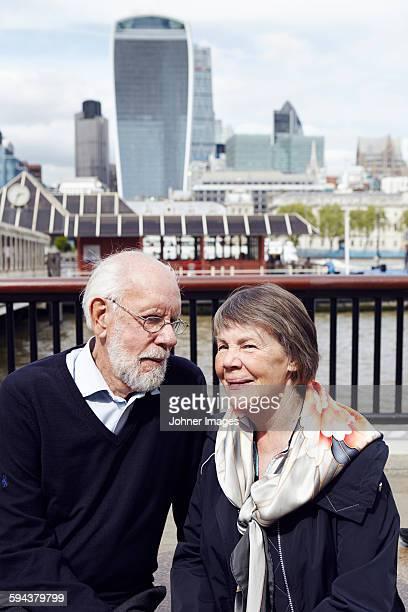 Senior couple, modern buildings on background