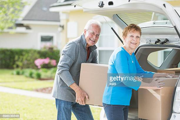 senior couple moving boxes in trunk of car - layoff stock photos and pictures