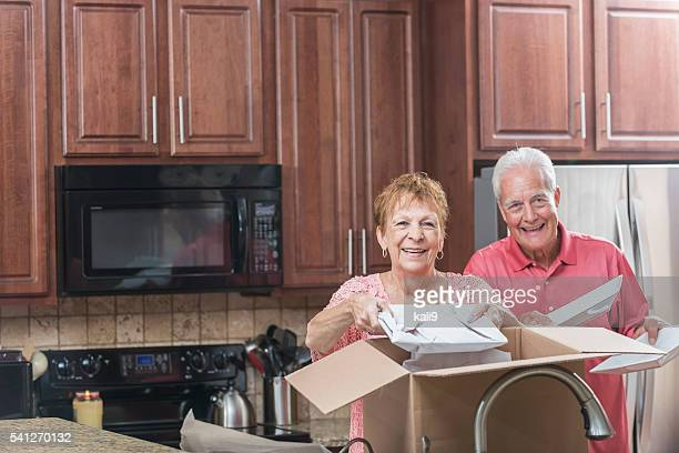 senior couple moving house, in the kitchen - layoff stock photos and pictures