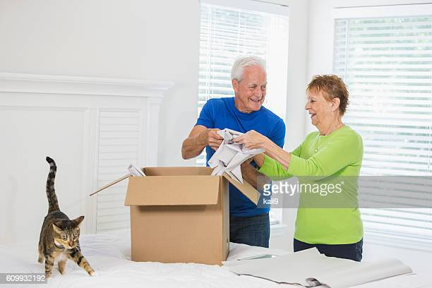 senior couple moving house, packing box - layoff stock photos and pictures