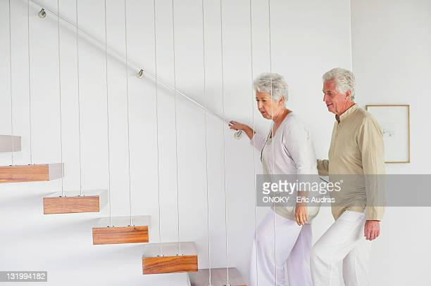 Senior couple moving up staircases