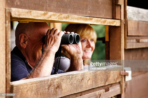 Senior couple observing wildlife through binoculars