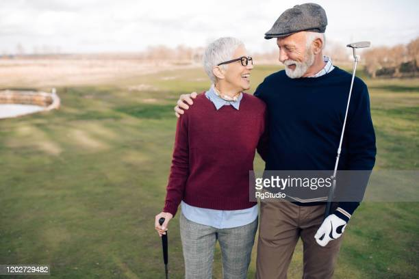 senior couple of golfers enjoying their play - golf stock pictures, royalty-free photos & images