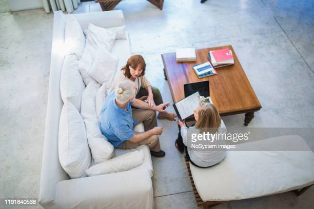 senior couple on a meeting with a legal adviser - mansion stock pictures, royalty-free photos & images