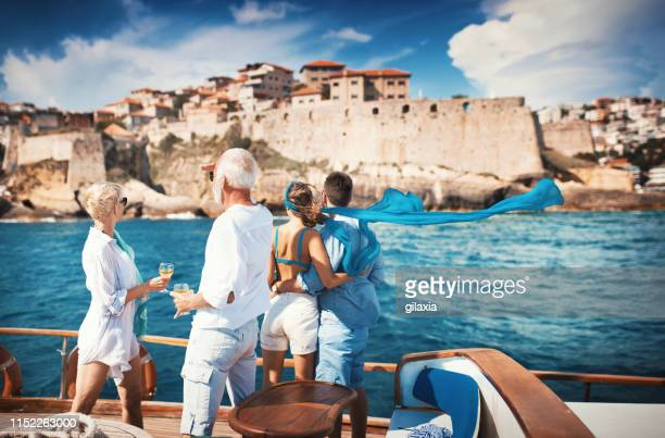 senior couple on a sailing cruise looking at coastline. - ricchezza foto e immagini stock