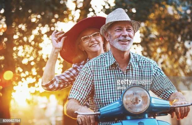 pareja senior en una moto scooter conducción por las calles. - pareja hombre mayor y mujer joven fotografías e imágenes de stock