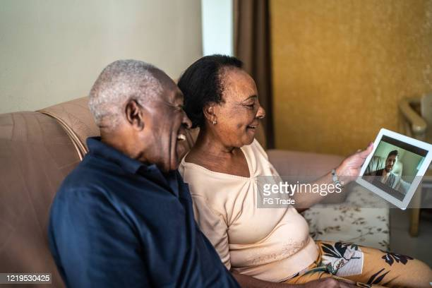 senior couple on a video calling using a digital tablet at home - stay at home order stock pictures, royalty-free photos & images