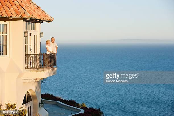 Senior couple on balcony of house overlooking ocean
