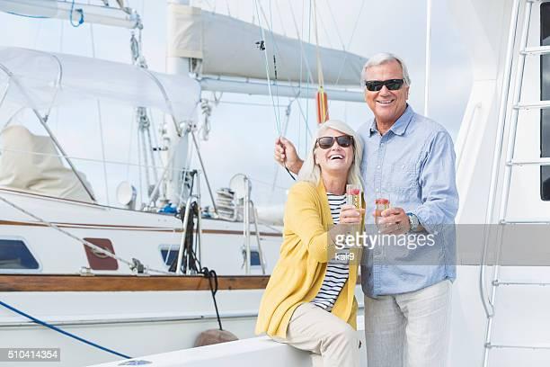 Senior couple on boat celebrating with champagne