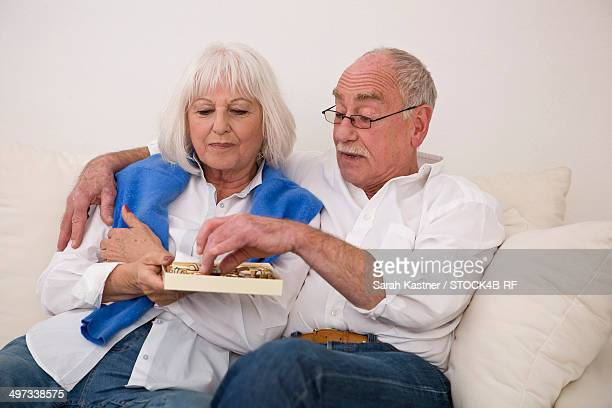 senior couple on couch nibbling sweets - couple chocolate stock pictures, royalty-free photos & images