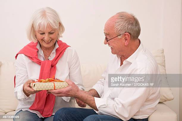 Senior couple on couch with gift