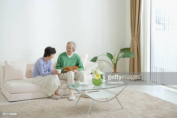 Senior couple on couch with their dog
