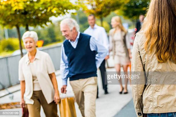 Senior Couple on Crowded City Street After Shopping