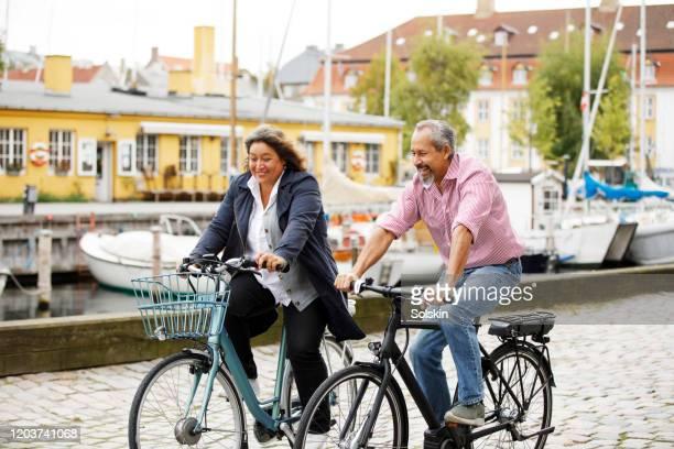 senior couple on electric bikes in old city area - heteroseksueel koppel stockfoto's en -beelden