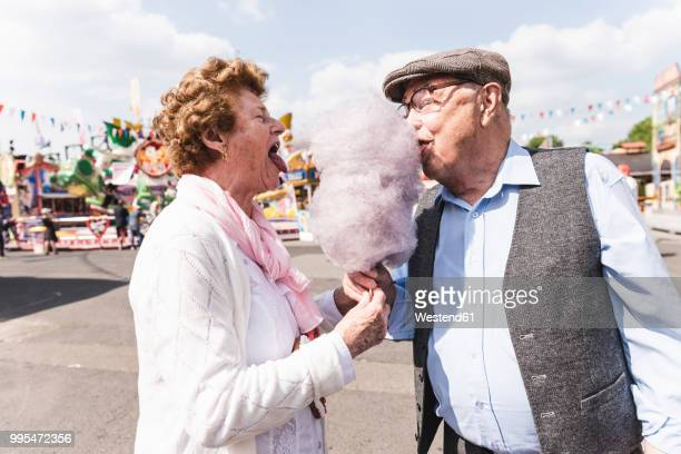 senior couple on fair eating together cotton candy - spaß stock-fotos und bilder