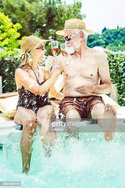 Senior couple on holidays having fun in jaccuzi toasting