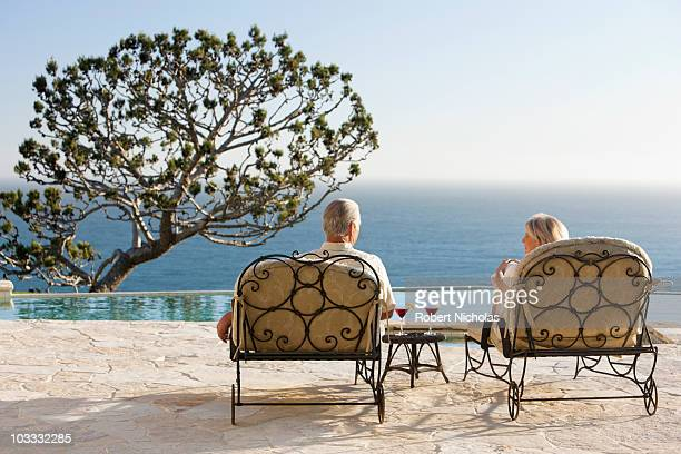 Senior couple on lounge chairs with cocktails at poolside overlooking ocean