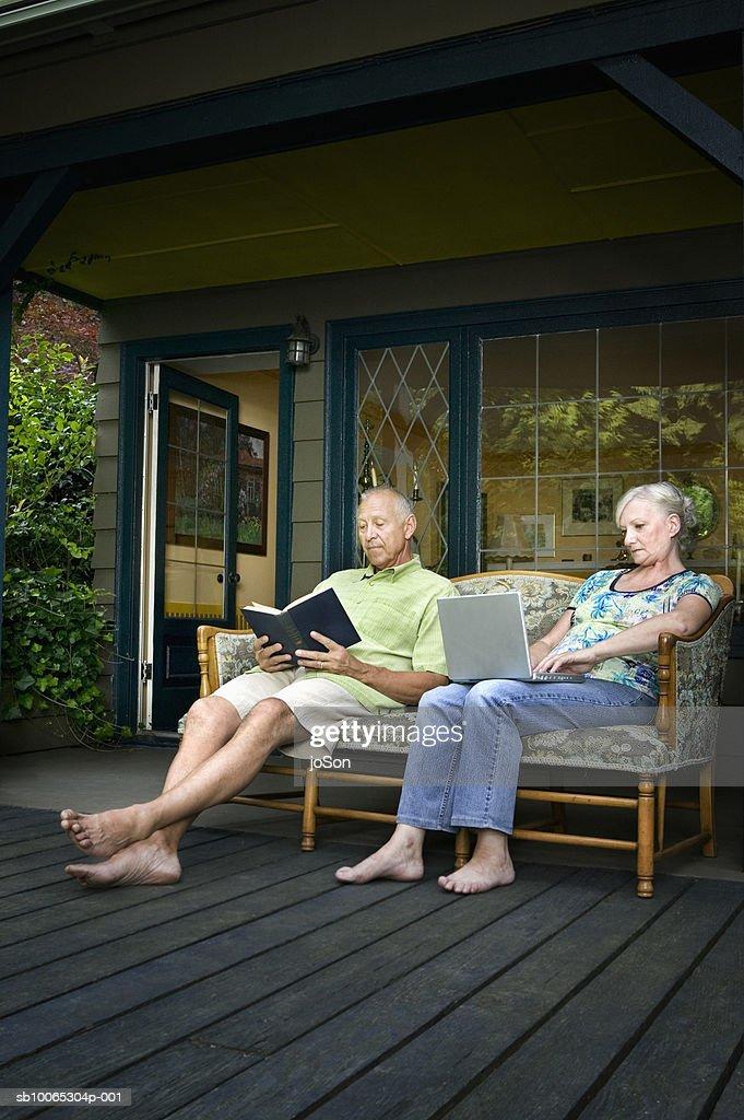 Senior couple on porch, man reading book, woman using laptop : Foto stock