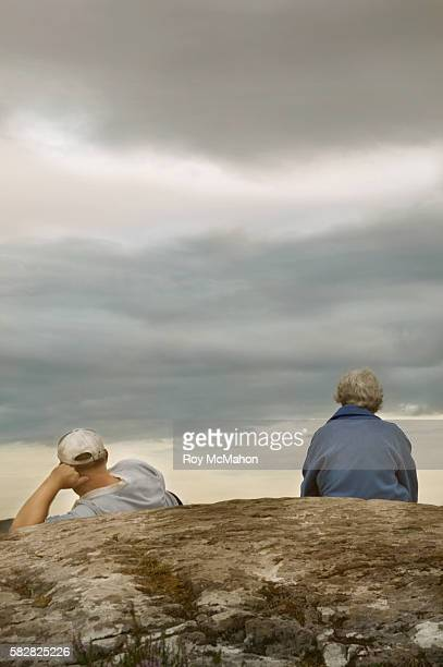 Senior Couple on Rock Under Cloudy Sky