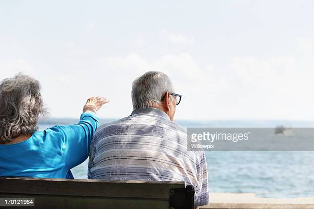 senior couple on shady bench watching lake boats - fat woman sitting on man stock pictures, royalty-free photos & images