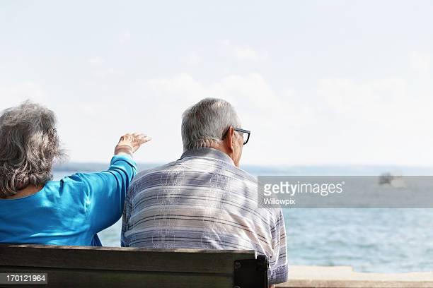 Senior Couple on Shady Bench Watching Lake Boats