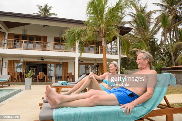 senior couple on sun loungers at the side of the pool - northern european descent stock pictures, royalty-free photos & images