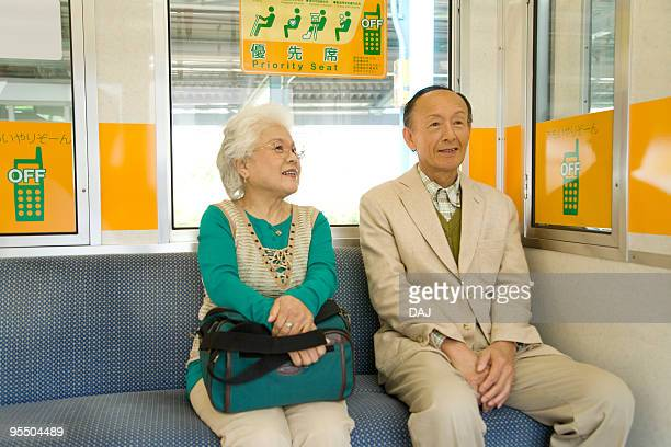 Senior couple on the train, sitting on the seat