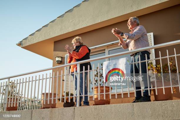 senior couple on their 70s clapping hands at balcony with a hand drawn rainbow fix at bannister - corona sun stock pictures, royalty-free photos & images