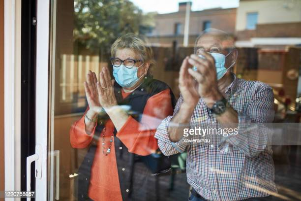 senior couple on their 70s clapping hands at home in quarantine covid-19 - illness prevention stock pictures, royalty-free photos & images