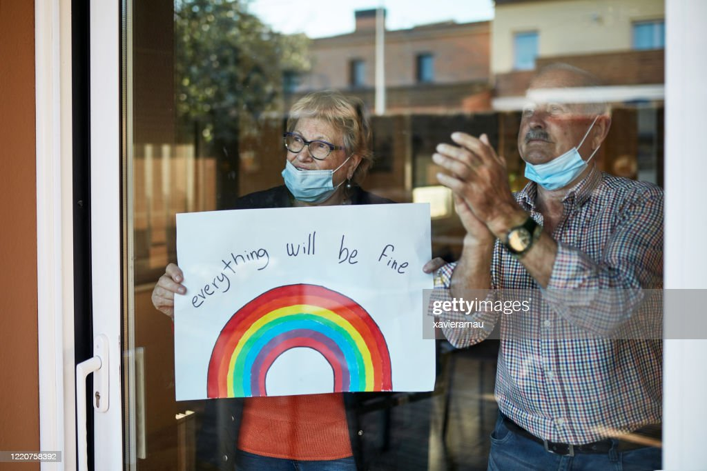 Senior couple on their 70s clapping hands at showing a hand drawn rainbow at home in quarantine : Stock Photo