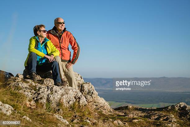 senior couple on top of mountain enjoying the view