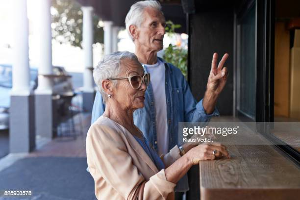 senior couple ordering coffee to-go, at street bakery - number 2 stock pictures, royalty-free photos & images
