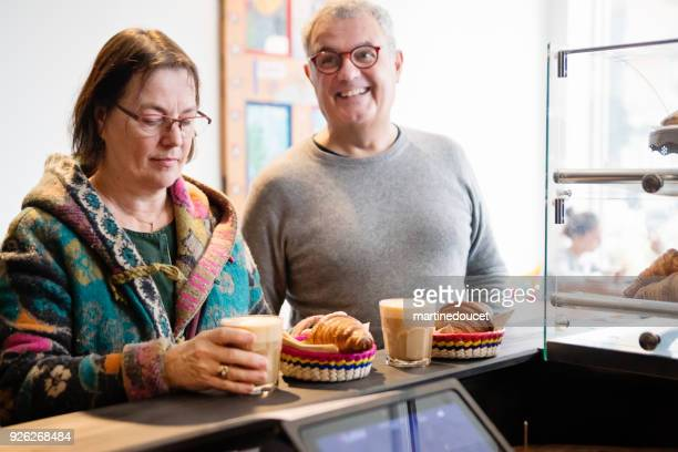 """senior couple ordering food in a small local bakery shop. - """"martine doucet"""" or martinedoucet stock pictures, royalty-free photos & images"""