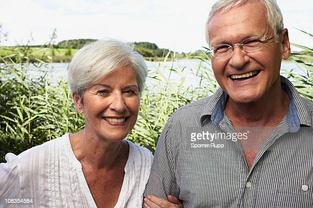 Senior couple outdoors smiling to camera