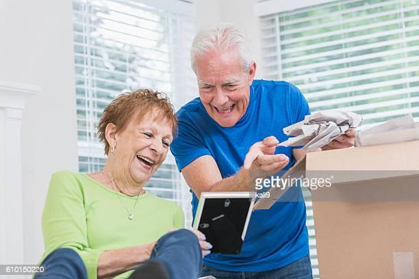 Seniorenpaar Packen box, schaut an Bilderrahmen