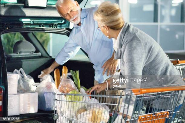 Senior couple packing groceries after shopping.