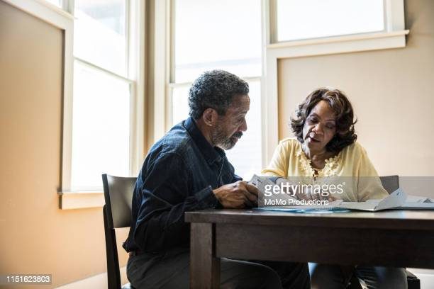 senior couple paying bills at home - aposentadoria - fotografias e filmes do acervo