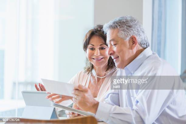 Senior couple paying bills online